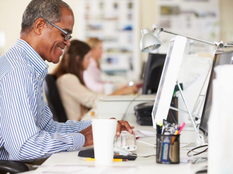 man-sitting-at-computer-desk-typing