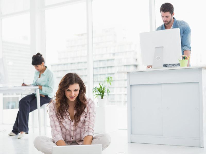 woman-sitting-at-desk-woman-sitting-on-floor-man-standing-desk